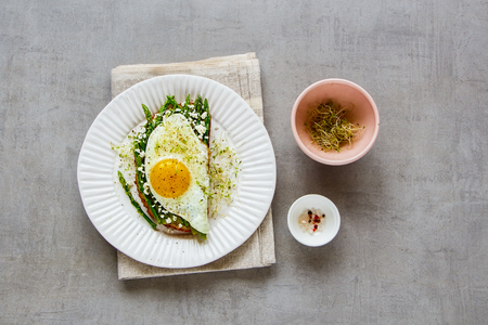 Flat lay of green aspargus, fried egg, feta cheese and micro greens spring sandwich on plate over light concrete background. Healthy eating, slimming, diet lifestyle concept. Top view Фото со стока