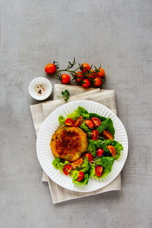 Healthy homemade cutlet vegan meatless served with tomato and lettuce salad on white plate over light concrete background. Top view, flat lay, vertical