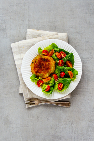 Plate of homemade cutlet vegan meatless served with tomato and lettuce salad on light concrete background. Top view, flat lay, vertical Stock Photo