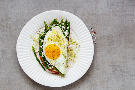 Delicious spring sandwich on plate close up. Green aspargus, fried egg, feta cheese and micro greens over light concrete background. Healthy eating, slimming, diet lifestyle concept. Top view
