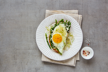 Spring sandwich on plate flat lay. Green aspargus, fried egg, feta cheese and micro greens over light concrete background. Healthy eating, slimming, diet lifestyle concept. Top view