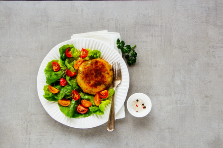 Roasted cutlet vegan meatless in white plate served with tomato and lettuce salad over light concrete background. Top view, flat lay Stock Photo