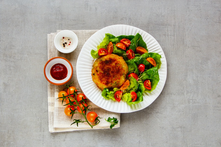 Flat-lay of roasted homemade cutlet vegan meatless served with tomato and lettuce salad on white plate over light concrete background. Top view