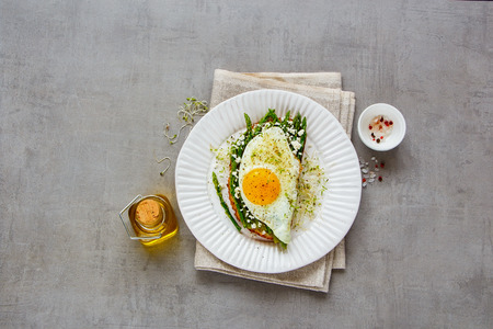 Flat lay of spring sandwich plate. Green aspargus, fried egg, feta cheese and micro greens over light concrete background. Healthy eating, slimming, diet lifestyle concept. Top view