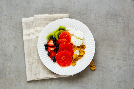 Flat lay of morning breakfast inspiration plate. Fresh various fruits, yougurt and coconut chia flakes over light concrete background. Healthy eating, slimming, diet lifestyle concept. Top view