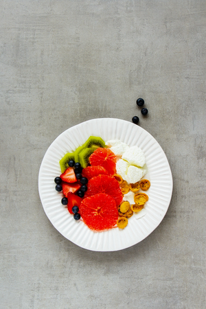 Healthy breakfast inspiration plate flat-lay. Yogurt, various fruits and coconut chia flakes over light concrete background. Healthy eating, slimming, diet lifestyle concept. Top view Фото со стока