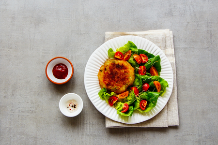 Flat lay of homemade cutlet vegan meatless served with tomato and lettuce salad on white plate over light concrete background. Top view Фото со стока