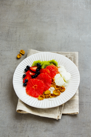 Breakfast inspiration plate with homemade yogurt, various fruits and coconut chia flakes over light concrete background. Healthy eating, slimming, diet lifestyle concept. Side view