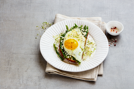 Close up of tasty spring sandwich plate. Green aspargus, fried egg, feta cheese and micro greens over light concrete background. Healthy eating, slimming, diet lifestyle concept. Side view Zdjęcie Seryjne