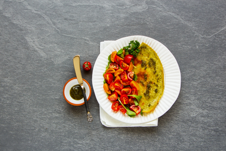 Healthy breakfast or diet lunch. Fla lay of omelette with pesto sauce, arugula and tomatoes salad on plate over grey concrete copy space background. Top view Фото со стока