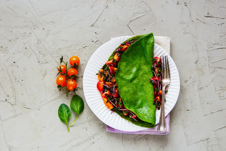 Flat-lay of green spinach omelette and fresh salad on white plate over light background. Detox, dieting, clean eating, vegetarian, fitness, healthy lifestyle concept. Top view
