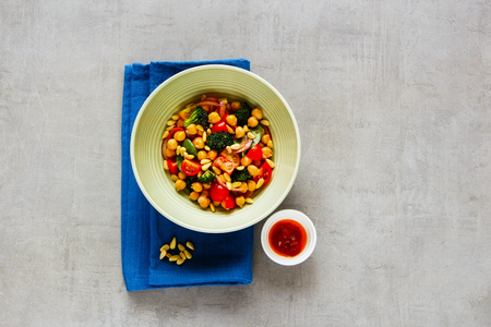 Vegan energy boosting salad bowl flat lay. Chickpeas, broccoli, tomatoes, red onion, pine nuts with honey dressing on light background. Clean eating, superfood, vegan, detox food concept