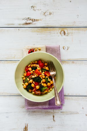 Chickpeas, broccoli, tomatoes, red onion, pine nuts with honey dressing in bowl on white wooden background flat lay. Vegan energy boosting salad. Clean eating, superfood, vegan, detox food concept