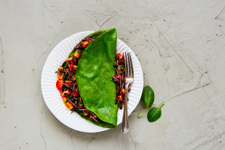 Green spinach omelette and fresh salad on plate over light concrete background. Detox, dieting, clean eating, vegetarian, fitness, healthy lifestyle concept. Top view, flat lay