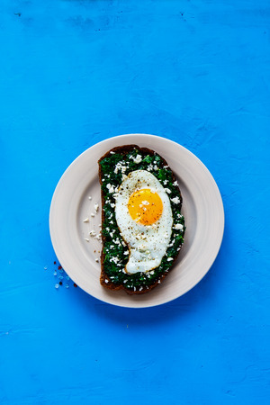 Healthy rye bread sandwich on bright blue background. Breakfast sandwich with kale, fried egg and feta cheese top view. Healthy eating, slimming, diet lifestyle concept. Flat lay style.
