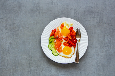 Morning breakfast in plate with smoked salmon, fried eggs, tomatoes and cucumber over light concrete background top view. Good fats healthy eating concept. Flat lay style. Stock Photo