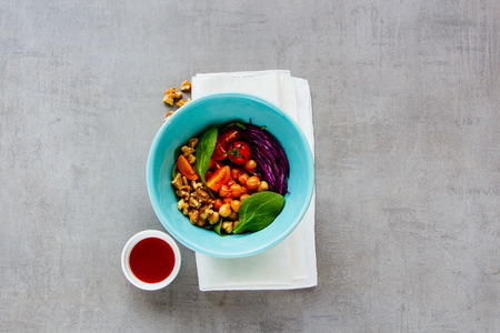 Vegan energy boosting buddha bowl. Healthy chickpeas, spinach, tomatoes, red cabbage, walnuts and honey dressing on light background. Diet, dieting concept. Vegan food, healthy eating. Top view, flat lay Stock Photo