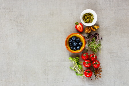 Flat-lay of clean eating healthy food selection. Micro greens, nuts, seeds, superfood, berry, tomatoes on light background. Ingredients for cooking. Food background with copy space. Top view