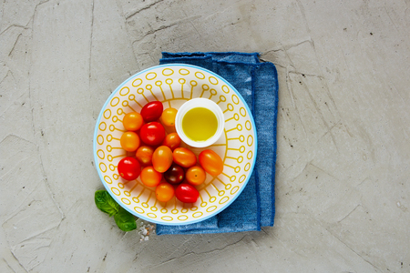 Fresh colorful tomatoes in bowl, olive oil and basil on light background with copyspace close up. Tasty tomato salad ingredients flat lay. Top view