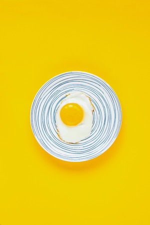 Plate of fried egg on yellow background flat lay. Food. Breakfast. Healthy food. Top view