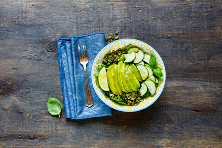 Green summer salad with avocado, arugula, cucumbers and pumpkin seeds and dressing in bowl over wooden background. Top view, flat lay style.