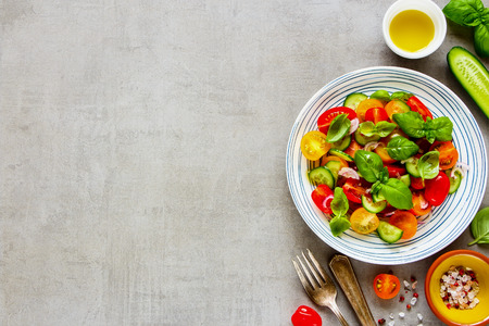 Healthy colorful salad in plate and ingredients on light background from above. Fresh cherry tomatoes, cucumbers, red onion, olive oil, basil and spices flat lay.