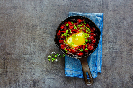 Vintage cast iron pan of shakshuka - eggs in tomato sauce, top view, copy space. Clean eating and healthy breakfast concept. Flat lay style. Banco de Imagens