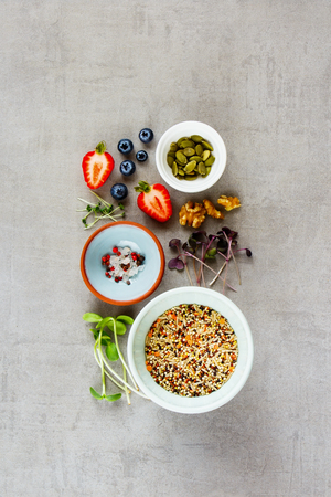 Clean eating healthy food selection flat-lay. Berry, micro greens, nuts, seeds, superfood, cereals on light background. Ingredients for cooking. Food background with copy space. Top view