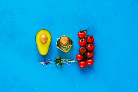 Raw Bio Food on blue background. Flat lay of avocado, cherry tomatoes, micro greens, olive oil and spices. Healthy food clean eating selection. Cooking ingredients. Top view.