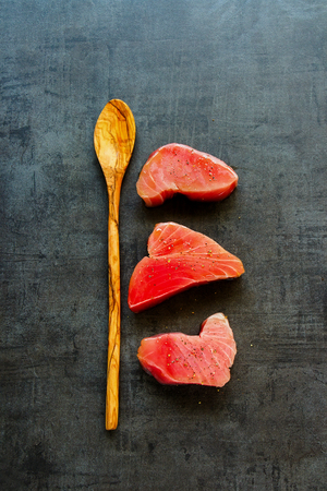 Wooden spoon and fresh Tuna fish steaks on vintage background flat lay. Healthy cooking. Food concept. Top view