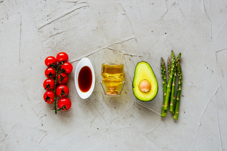 Cherry tomatoes, dressing, olive oil, avocado and aspargus flat lay. Healthy food clean eating selection. Cooking ingredients. Top view. Raw Bio Food on light background. Фото со стока