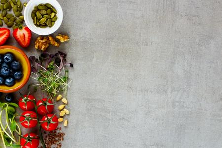 Gesundes Essen sauberes Essen Auswahl Nahaufnahme. Beere, Gemüse, Mikrogrün, Nüsse, Samen, Superfood auf hellem Hintergrund. Zutaten zum Kochen. Lebensmittelhintergrund mit Kopierraum. Draufsicht, flach liegen Standard-Bild