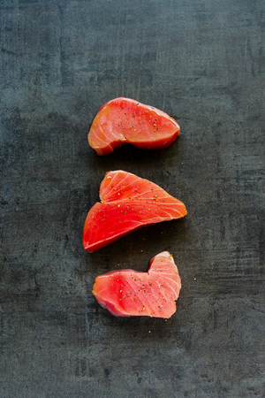 Steaks of Raw Tuna fish on vintage background flat lay. Healthy cooking. Food concept. Top view