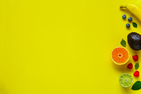 Creative layout made of organic tropical fruits on yellow background. Banana, orange, lime, avocado, raspberry, blueberry. Food concept. Flat lay, top view