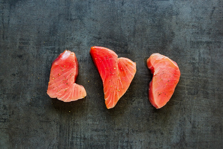 Raw Tuna fish steaks on vintage background flat lay. Healthy cooking. Food concept. Top view Stock Photo