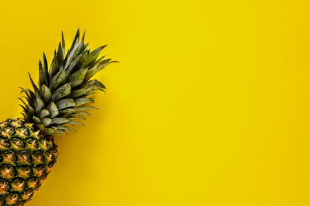 Organic pineapple on yellow background flat-lay. Tropical fruit from above. Useful natural food. One whole object. Style minimalist.