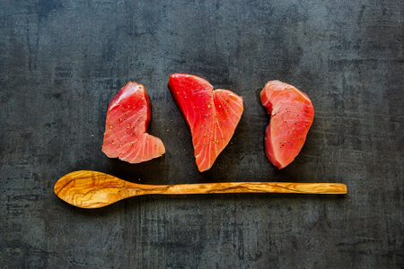 Flat lay of wooden spoon and fresh Tuna fish steaks on vintage background. Healthy cooking. Food concept. Top view