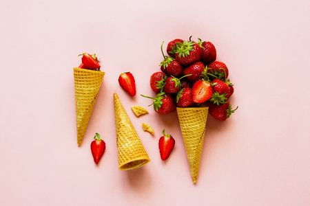 Spring or summer composition on pastel light pink background flat lay. Waffle sweet cone with fresh strawberry from above. Holiday mood concept.