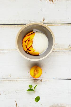 Breakfast bowl. Greek yogurt and fresh peach flat lay. Healthy food concept.