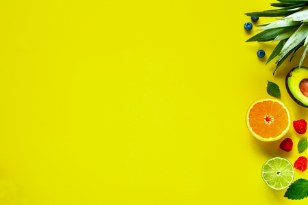 Creative layout made of various tropical fruits. Flat-lay of pineapple, banana, orange, lime, avocado, raspberry, blueberry on yellow background. Food concept. Top view