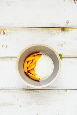 Breakfast. Greek yogurt and fresh peach in bowl flat lay. Healthy food concept. Stock Photo
