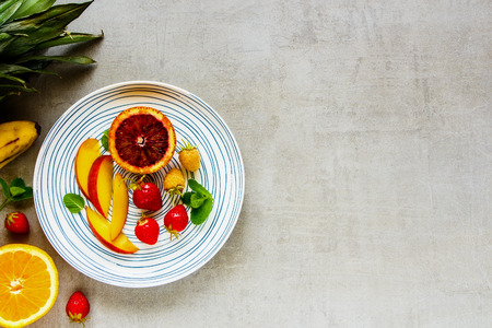 Plate of fresh tropical fruits and organic berries flat-lay. Bio food concept. Top view