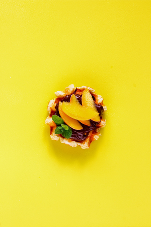 Belgian waffle with chocolate and peach on yellow background flat-lay