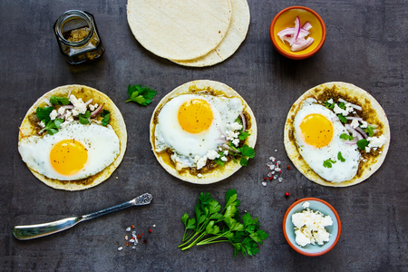 Flat lay of corn tortillas with fried eggs, pesto sauce and feta cheese Imagens