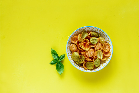Bowl of veggie chips on yellow background flat lay
