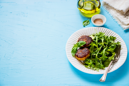 Close up of homemade cutlets and green salad on blue background Stock Photo