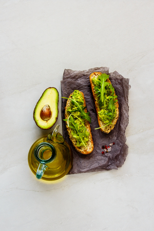 Fresh toasts with avocado and arugula flat lay. Good fats raw healthy eating concept.