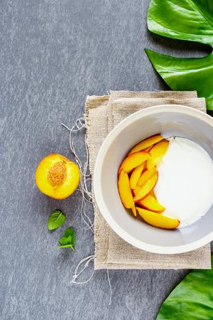 Breakfast table. Natural yogurt and fresh peach bowl flat-lay. Healthy food concept. Stock Photo