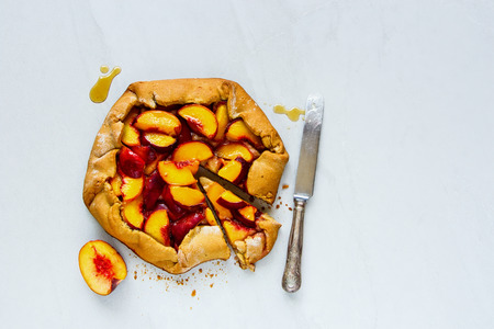 Homemade peach galette sweet cake close up. Seasonal Fall or Autumn dessert. Flat lay