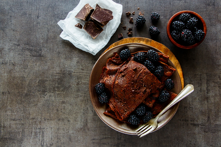 Flat-lay of chocolate crepes. Thin pancakes, chocolate bars and fresh blackberries